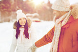 happy couple walking along snowy winter field