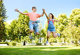 happy teenage couple jumping at summer park