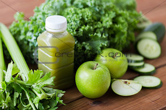 close up of bottle with green juice and vegetables