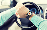 close up of man driving car with gps on smartwatch