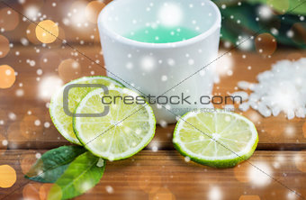 citrus body lotion in cup and limes on wood