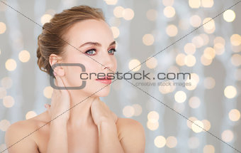 beautiful woman touching her neck over lights