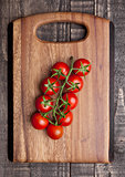 Fresh healthy organic tomatoes on wooden kitchen board