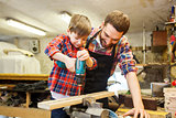 father and son with drill working at workshop