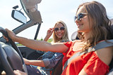 smiling young women driving in cabriolet car
