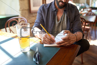 close up of man with beer and notebook at pub