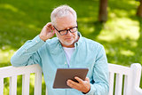 senior man with tablet pc at summer park