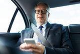 senior businessman texting on smartphone in car