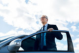 senior businessman getting into car