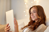 happy young woman with tablet pc in bed at home