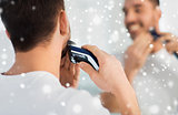 close up of man shaving beard with trimmer