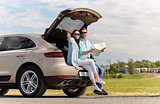 happy man and woman with road map at hatchback car