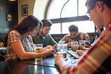 friends with smartphones and beer at bar or pub