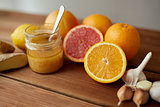 honey, citrus fruits, ginger and garlic on wood