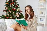 happy woman reading book at home for christmas