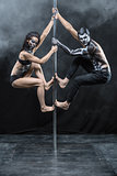 Posing of pole dance couple in dark studio