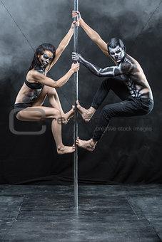 Posing of pole dance couple in dark studio