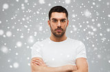 young man with crossed arms over snow background