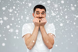 scared man in white t-shirt over snow background