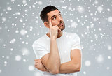 man thinking over snow on gray background