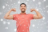 smiling man showing biceps over snow background