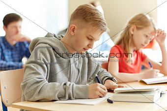 group of students with books writing school test