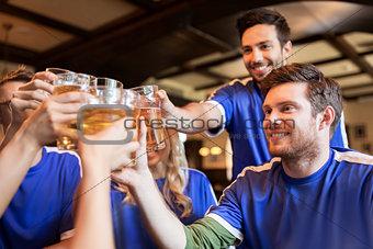 football fans clinking beer glasses at sport bar