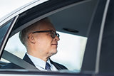 senior businessman driving on car back seat