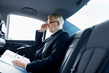 senior businessman with papers driving in car