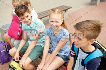 group of happy elementary school students talking