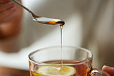 close up of woman adding honey to tea with lemon