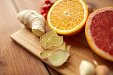 citrus fruits, ginger and garlic on wood
