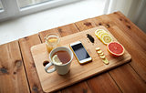 smartphone with cup of lemon tea, honey and ginger