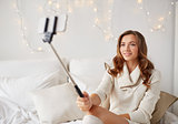 happy woman taking selfie by smartphone at home