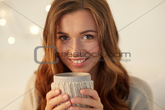 close up of woman with tea or coffee cup at home