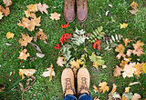 feet in boots with rowanberries and autumn leaves