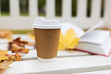 coffee drink in paper cup on bench at autumn park