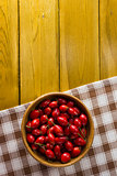Ripe rosehips in wooden plate