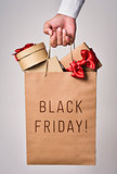 shopping bag full of gifts and text black friday