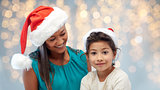 happy mother and little girl in santa hats