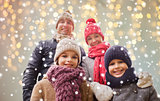 happy family over christmas lights and snow