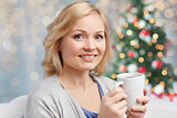happy woman with cup of tea or coffee at christmas
