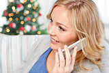 smiling woman calling on smartphone at christmas