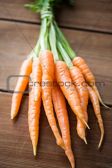 close up of carrot bunch on wooden table