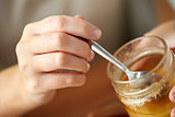 close up of woman hands with honey and spoon