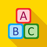 Children's toy cubes with letters on a yellow background