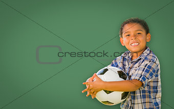 Cute Young Mixed Race Boy Holding Soccer Ball In Front of Blank