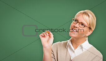 Attractive Young Woman with Pencil In Front of Blank Chalk Board