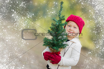 Baby Girl In Mittens Holding Small Christmas Tree with Snow Effe