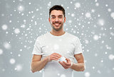 happy young man with cream jar over snow